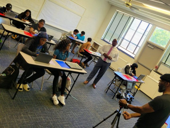 children siting in a classroom being filmed