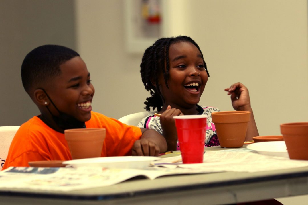 two children laughing while painting pots